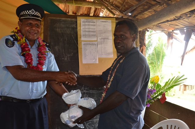 RSIPF Assistant Commissioner Gabriel Manelusi gifts footballs to a chief during community consultation session